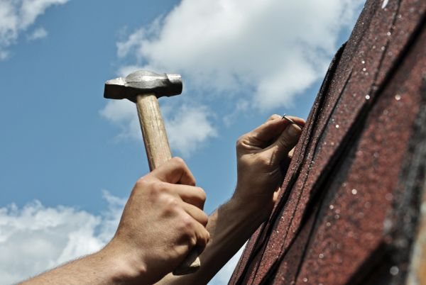 roofer hammering a shingle